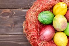 Colorful easter eggs in basket on wooden background. Eggs handmade new style of colouring . Pattern, easter concept. Colorful easter eggs in basket on wooden royalty free stock images