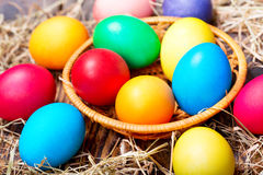 Colorful Easter eggs in a basket. On wooden table Stock Image