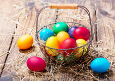 Colorful Easter eggs in a basket. On wooden table Royalty Free Stock Photos