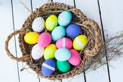 Colorful easter eggs in basket Stock Photos