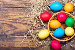 Colorful Easter eggs in a basket. On wooden table, top view Royalty Free Stock Images