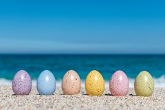 Colorful Easter eggs on the beach in sunny day. stock photo