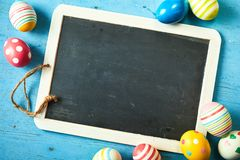 Colorful Easter eggs and a blank kids slate stock photos