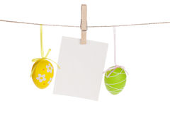 Colorful easter eggs and blank photo frame hanging on rope Royalty Free Stock Photography