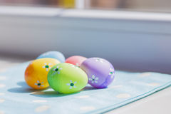 Colorful easter eggs on blue fabric near window Stock Photography