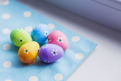 Colorful easter eggs on blue fabric near window Royalty Free Stock Photo