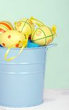 Colorful easter eggs in a blue pail Stock Images