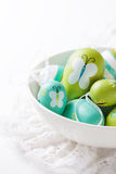 Colorful Easter eggs in a bowl on a bright background Stock Image
