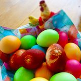 Colorful easter eggs in bowl with decorative chicken royalty free stock photography
