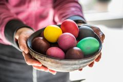 Colorful Easter eggs in bowl in woman`s hands royalty free stock images