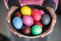 Colorful Easter eggs in bowl in woman`s hands royalty free stock photo