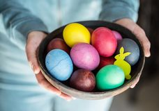 Colorful Easter eggs in bowl in woman`s hands royalty free stock image