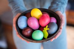 Colorful Easter eggs in bowl in woman`s hands royalty free stock photography