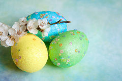 Colorful easter eggs and branch with flowers. Painted easter eggs and branches of spring sakura closeup on a light blue background with space for congratulation Stock Photos