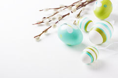 Colorful Easter eggs on a bright background with willow branches and copy space Royalty Free Stock Image