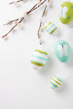 Colorful Easter eggs on a bright background with willow branches and copy space Royalty Free Stock Photos