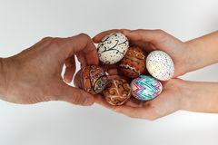 Colorful Easter eggs on burlap, female hand chose and pick one egg. Colorful Easter eggs in female hands, male hand chose and pick one egg against white Stock Photos