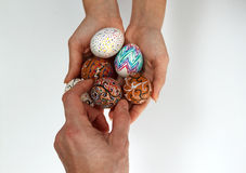 Colorful Easter eggs on burlap, female hand chose and pick one egg Royalty Free Stock Photo