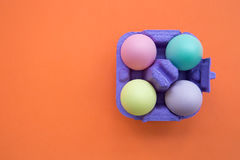Colorful easter eggs in carton box on bright orange background. Overhead shot of cute easter eggs stock image