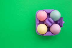 Colorful easter eggs in carton box on green background. Overhead shot of cute easter eggs royalty free stock image