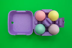Colorful easter eggs in carton box on green background. Overhead shot of cute easter eggs royalty free stock images