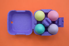 Colorful easter eggs in carton box on orange background. Overhead shot of cute easter eggs Stock Images