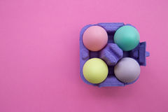 Colorful easter eggs in carton box on pink background. Overhead shot of cute easter eggs Stock Photos