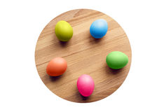 Colorful easter eggs on a circular wooden board. Isolated Royalty Free Stock Images
