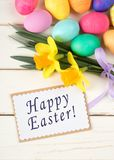 Colorful Easter Eggs and Daffodil Flowers still life on Rustic White Board Background with Happy Easter in words or text on greeti. Ng card or name tag. Vertical Stock Photos