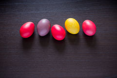 Colorful Easter eggs on dark rustic wooden background. Colorful red, pink, violet and yellow Easter eggs on dark rustic wooden background stock photography