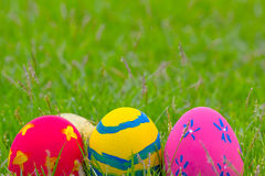 Colorful Easter eggs decorated with flowers in the grass. On a yellow background Stock Image