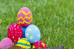 Colorful Easter eggs decorated with flowers in the grass. On a yellow background Royalty Free Stock Photography