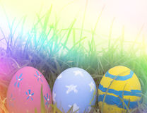 Colorful Easter eggs decorated with flowers in the grass. On a yellow background Royalty Free Stock Photos