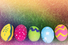 Colorful Easter eggs decorated with flowers in the grass. On a yellow background Stock Photos