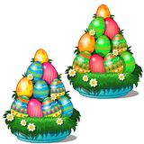 Colorful Easter eggs with different patterns stacked in cone on plate with grass and flowers. Symbol for holiday. Colorful Easter eggs with different patterns Stock Photography