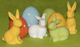 Colorful easter eggs and Easter bunnies in front of a green background. Four colorful ceramic easter eggs and four Easter bunnies in front of a green background stock photos