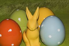 Colorful easter eggs and an Easter bunny in front of a green background. Colorful ceramic easter eggs and an Easter bunny in front of a green background stock image