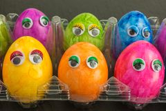 Colorful easter eggs with eyes in plastic container Stock Images