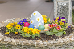 Colorful easter eggs in a flower pot with horned violet flowers Royalty Free Stock Image