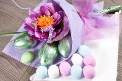 Colorful Easter Eggs with flowers and chocolate eggs Stock Images
