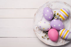 Colorful Easter eggs and flowers of the field in the plate. Royalty Free Stock Photography