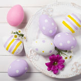 Colorful Easter eggs and flowers of the field in the plate Royalty Free Stock Photography