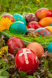 Colorful easter eggs with flowers, outside. Red egg with a cross