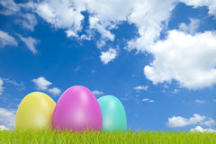 Colorful easter eggs in front of a cloudy sky with Royalty Free Stock Photo