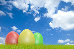 Colorful easter eggs in front of a cloudy sky Royalty Free Stock Images