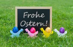 Colorful Easter eggs and german text: happy easter. Eastercard with chalkboard and colorful Easter eggs with german text: Happy Easter Royalty Free Stock Photography