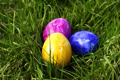 Colorful easter eggs in grass. Overhead view of three colorful hand painted Easter eggs nestling in grass royalty free stock photography