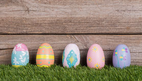 Colorful Easter Eggs on Grass. Against a wood background Stock Photo