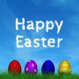 Colorful Easter Eggs. 4 Colorful Easter Eggs in the grass with the blue sky and white clouds Royalty Free Stock Photography