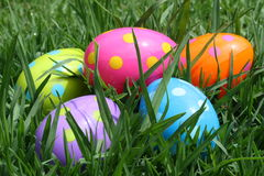 Colorful Easter Eggs in the grass. Five colorful purple, lilac' blue, orange and yellow Easter Eggs hidden in long grass Royalty Free Stock Photos